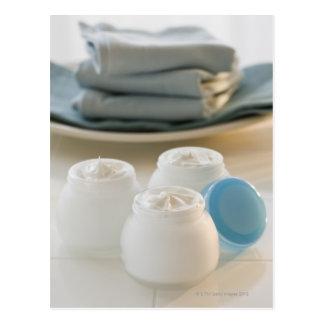 Los tarros de hidratación baten y pila de toallas tarjeta postal