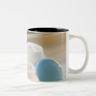 Los tarros de hidratación baten y pila de toallas taza