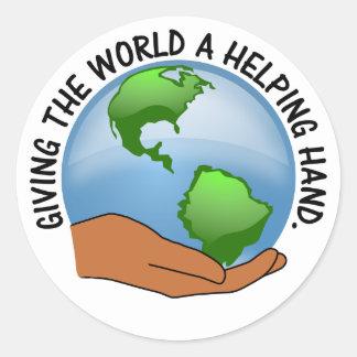 Los voluntarios dan a mundo una mano amiga pegatina redonda