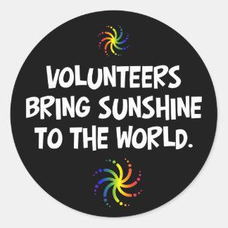 Los voluntarios traen la sol al mundo pegatina redonda