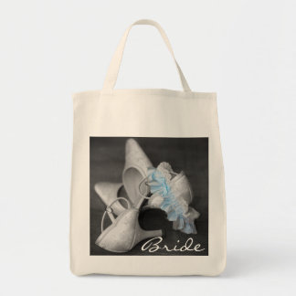 Los zapatos y la novia nupciales de la liga llevan bolsa tela para la compra