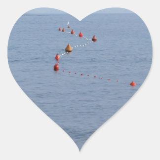 Lots of mooring buoys floating on water in marina heart sticker