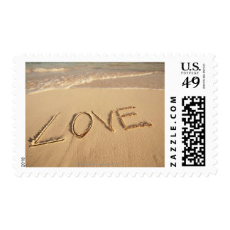 'Love' sand written on the beach with incoming Postage
