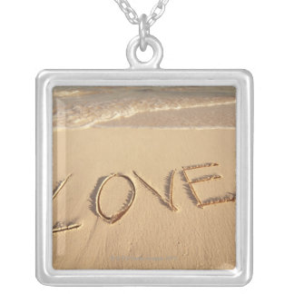 'Love' sand written on the beach with incoming Silver Plated Necklace