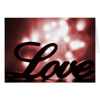 Love sign with red sparkle lights behind greeting card