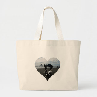 Love (silhouette of young lovers on beach) canvas bags