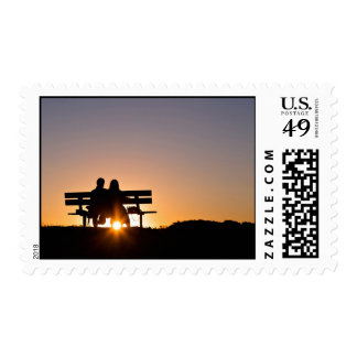 Love Themed, A Couple Sits On A Bench As The Sun G Stamps