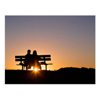 Love Themed, A Couple Sits On A Bench As The Sun G Postcard