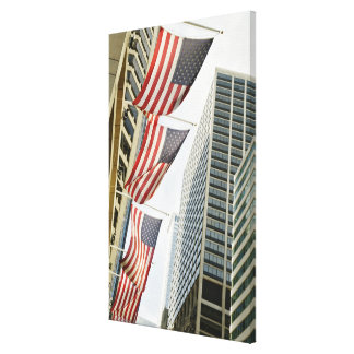Low angle view at American flags in downtown Canvas Prints
