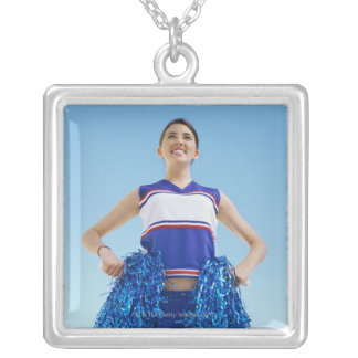 Low angle view of a cheerleader holding her silver plated necklace