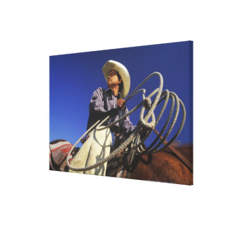 Low angle view of a cowboy riding a horse, canvas print
