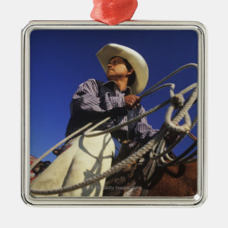 Low angle view of a cowboy riding a horse, square metal christmas ornament