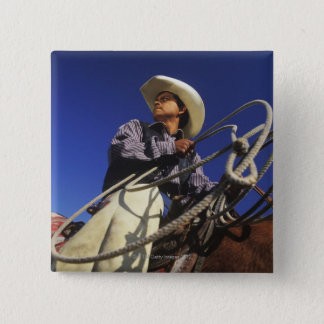 Low angle view of a cowboy riding a horse, pinback button