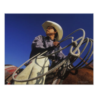 Low angle view of a cowboy riding a horse, poster