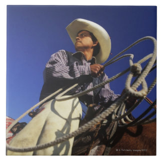 Low angle view of a cowboy riding a horse, large square tile