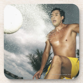 Low angle view of a man playing beach volley beverage coaster
