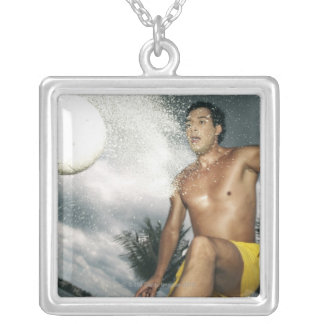Low angle view of a man playing beach volley square pendant necklace