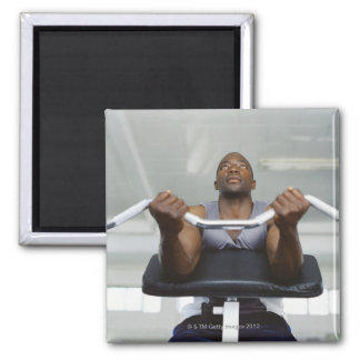 Low angle view of a mid adult man exercising in fridge magnets