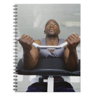 Low angle view of a mid adult man exercising in spiral notebooks