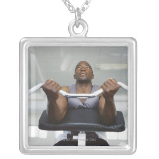 Low angle view of a mid adult man exercising in square pendant necklace
