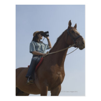 Low angle view of a teenage girl riding a horse postcard