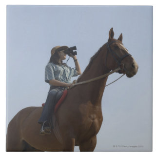 Low angle view of a teenage girl riding a horse large square tile