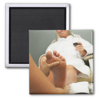 Low angle view of man receiving foot massage magnet