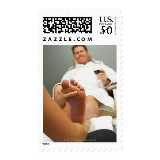 Low angle view of man receiving foot massage postage