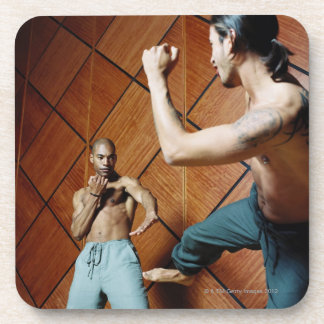 Low angle view of two young men practicing drink coasters