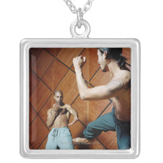 Low angle view of two young men practicing square pendant necklace