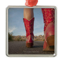 Low-angle view of woman wearing cowboy boots metal ornament