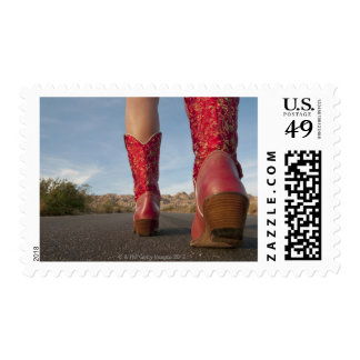 Low-angle view of woman wearing cowboy boots postage