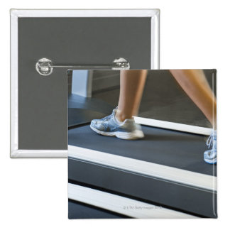 Low section of woman walking on treadmill 2 button