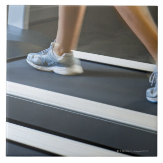 Low section of woman walking on treadmill 2 large square tile