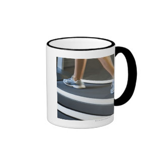 Low section of woman walking on treadmill 2 mugs
