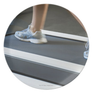 Low section of woman walking on treadmill 2 plate