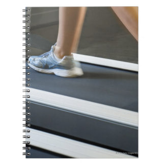 Low section of woman walking on treadmill 2 spiral notebook