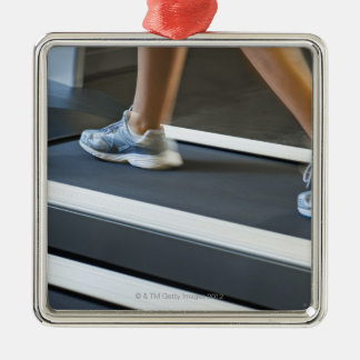Low section of woman walking on treadmill 2 square metal christmas ornament