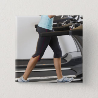 Low section of woman walking on treadmill button