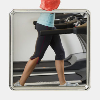 Low section of woman walking on treadmill square metal christmas ornament