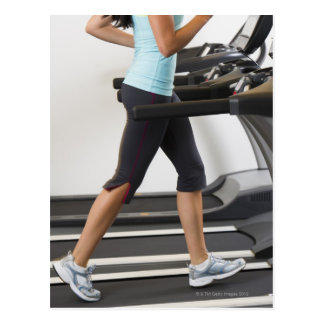 Low section of woman walking on treadmill postcard