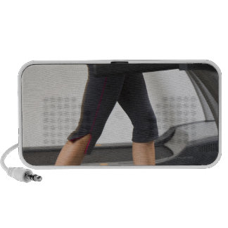 Low section of woman walking on treadmill PC speakers