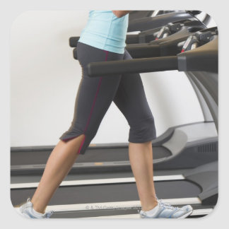 Low section of woman walking on treadmill square sticker