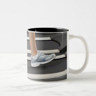 Low section of woman walking on treadmill Two-Tone coffee mug