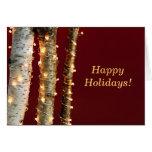 Luces de navidad en troncos del abedul felicitación