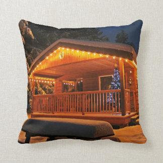 Luces de navidad hermosas en la cabaña de madera e cojines