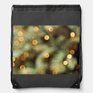 Luces del oro del centelleo en un árbol de navidad mochila