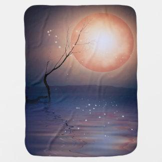 Luna chispeante de la fantasía rosada y azul sobre manta de bebé