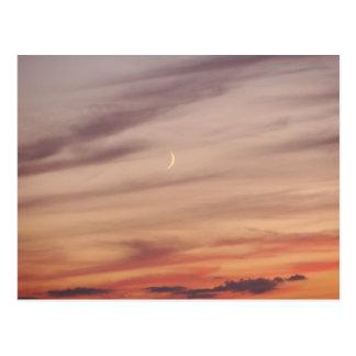 Luna creciente en la oscuridad postal