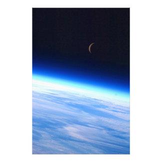 Luna creciente sobre una tierra que brilla intensa fotografia